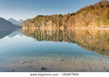 Crystal clear water reflection in Hohenschwangau lake with bavarian alps in Germany