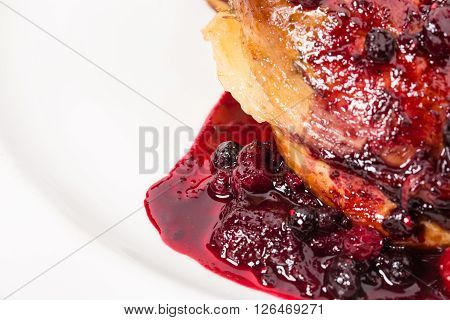 Delicious duck leg confit with red sauce and stewed berries. Macro. Photo can be used as a whole background.