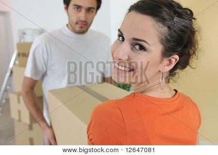 Couple lifting a carton