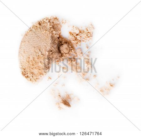 scattered beige eye shadow on a white background