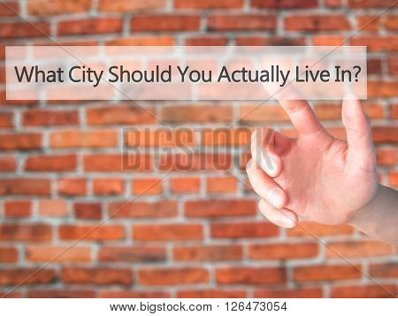 What City Should You Actually Live In - Hand Pressing A Button On Blurred Background Concept On Visu