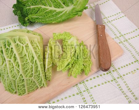 Sliced savoy cabbage on wooden board and a knife