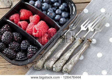 Red fruits in plastic tray: blackberries, raspberries and blueberries.