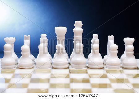 White chess pieces made from Onyx on board against dark background