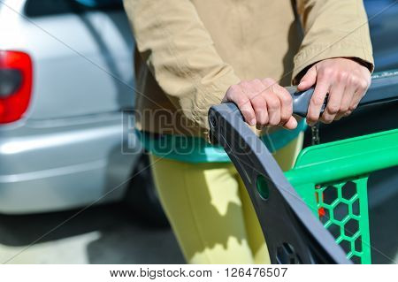 Young woman holding shopping push cart closeup picture of hands with car on background