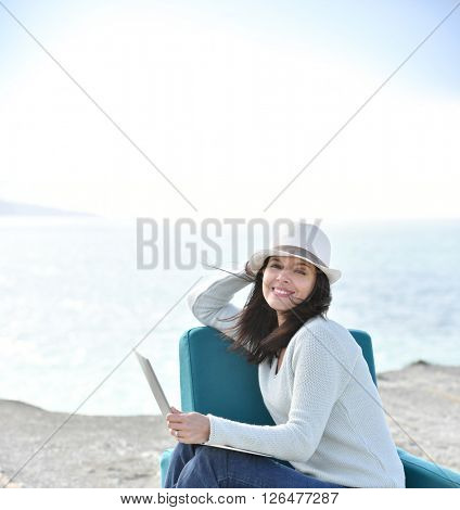 Woman with hat sitting by the sea in armchair
