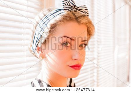 Closeup image of cute blond pinup woman face with green eyes looking pensively towards camera