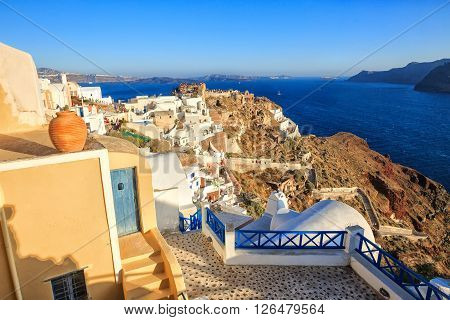 Oia, Santorini, Greece - July 04, 2013: Tourists enjoy the sunset passed from the best mountainside in Oia, Santorini island