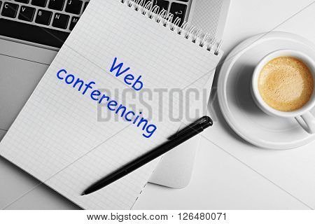 Web conferencing written in notebook, laptop and cup of coffee on table, top view