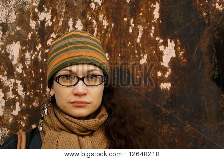 beautiful young adult woman in a cap and glasses against a grungy rusty wal