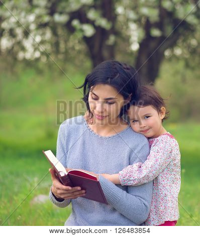 mother with daughter read a book on the meadow