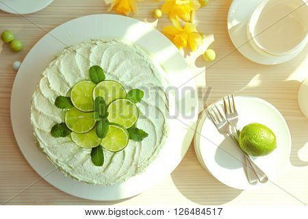 Lime cake with white tableware on a wooden table