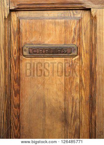 Old wooden door with a metallic mailbox