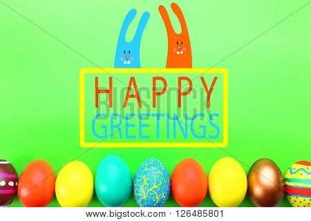 Easter greeting card. Painted eggs on green background