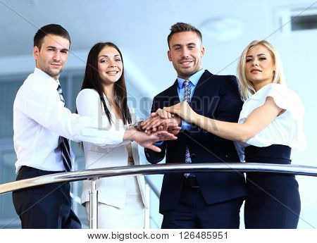 Portrait of positive business group standing on stairs of modern building
