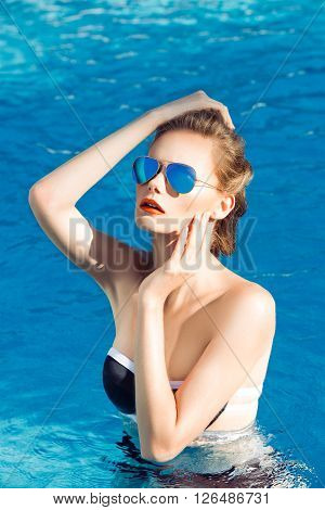 Beautiful brown hair woman in water wearing bikini. Young girl model in sunglasses and elegant black and white sexy swimsuit lingerie in swimming pool with clear deep blue water. Full relax. Vintage.