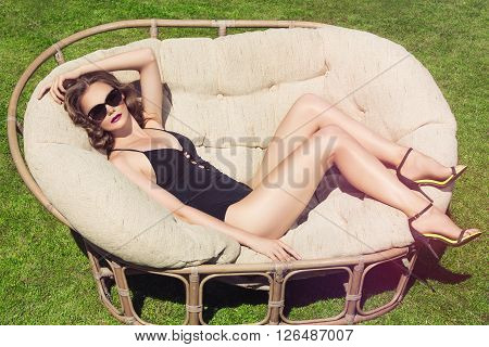 Beautiful brown hair woman wearing bikini. Young girl model in sunglasses and elegant black sexy swimsuit lingerie. Full relax. Vintage. Sunbathing on a lounger.