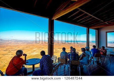BETANCURIA, FUERTEVENTURA ISLAND, SPAIN - SIRCA JANUARY 2016: Tourists enjoy great view on the central part of Fuerteventura island near Betancuria village from the cafe at Morro Velosa viewpoint