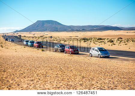 CORRALEJO, FUERTEVENTURA ISLAND, SPAIN - SIRCA JANUARY 2016: Road with cars on Corralejo desert on Fuerteventura island