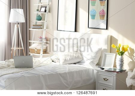 Bedroom interior in light tones with furniture and pictures on the wall