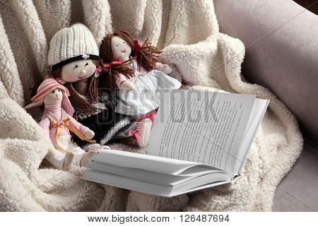 Rag dolls with fairy tales book on bedspread. Childhood concept