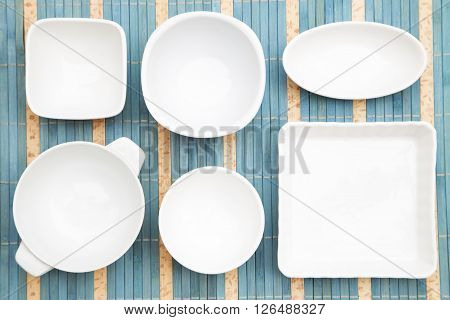 White dishes on a blue straw background