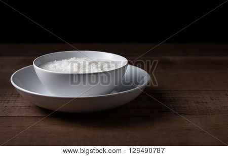 Gruel in white bowl on wooden background