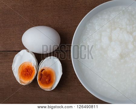 Salted egg and gruel chinese food on wooden background.