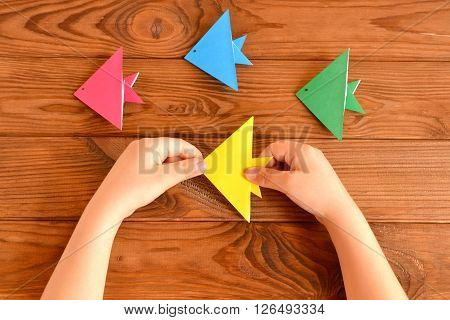 Origami colorful fish. Child holds an yellow origami fish in his hands. Brown wooden background