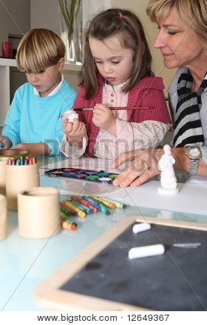 Senior woman making watercolors with children