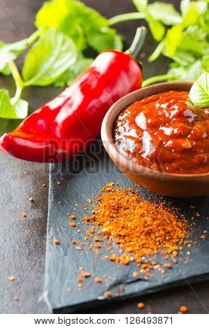 Fresh, dry ground and salsa chili on stone background