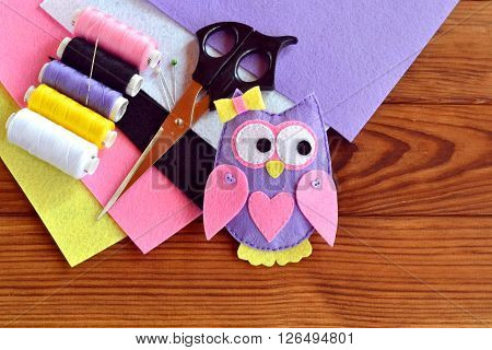 Cute felt owl toy. Scissors, sheets of felt, thread, needles - sewing kit.