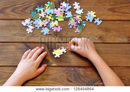 Child holding puzzles in hands. A set of jigsaw puzzles on wooden table