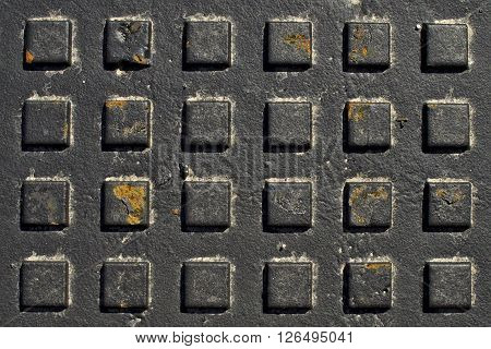 Manhole cover texture. Grid of squares on black iron.