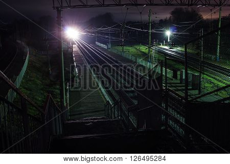 Railway station at spring night with a passing train