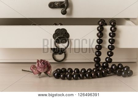 Black pearls necklace in a wooden casket as a background