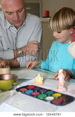Senior man making watercolor with a little boy