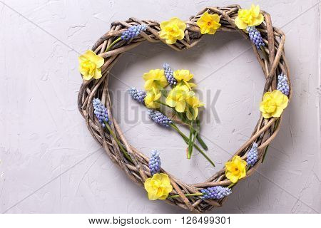 Big decorative heart and bright spring flowers on grey textured background. Selective focus. Place for text.