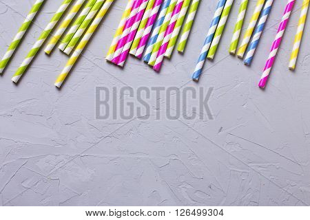Border from bright pink yellow blue and green paper straws aon textured grey slate background. Selective focus. Place for text.