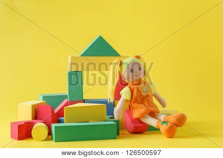 Toy house and doll with blocks on yellow background