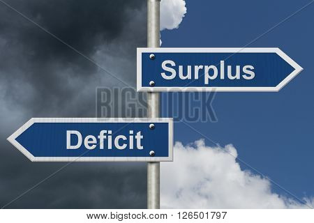 Difference between a Surplus and a Deficit Two Blue Road Sign with text Surplus and Deficit with bright and stormy sky background