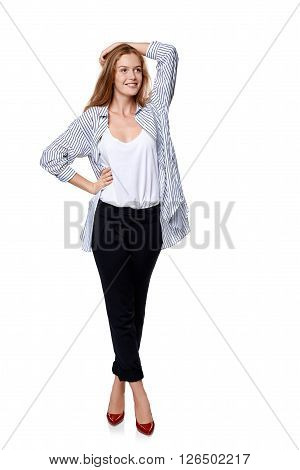 Full length of beautiful blond female fashion model posing over white background looking to the side at blank copy space