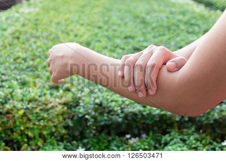 Concept of Woman arm pain in park.