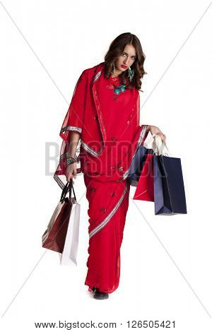 Shopping. Fashion brunette woman in red sari, isolated on white background