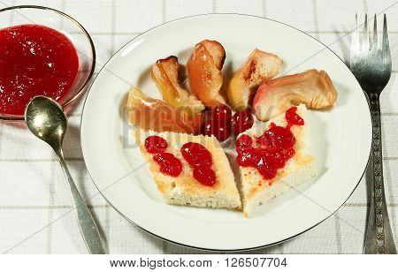 Baked caramel apple slices in plate and sauce from fresh cranberries. A spoon and a fork. Serving on the light-colored tablecloths.