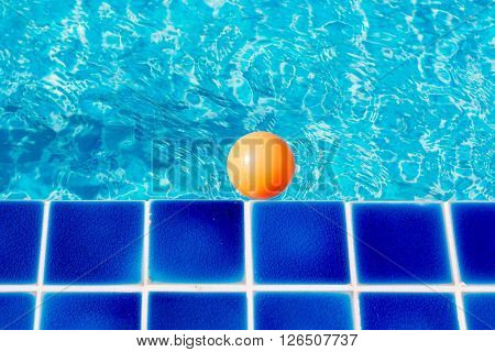 orange plastic ball in swiming pool and blue water