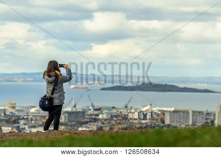 An unidentified female taking a photo using a smaert phone from Calton Hill in Edinburgh.