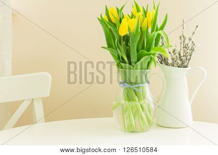fresh yellow  tulips and willow catkins  in pot on white table