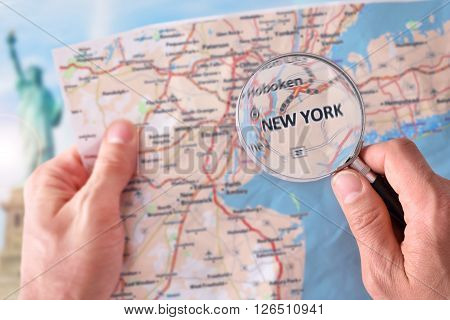 Man Consulting A Map Of New York With Magnifying Glass