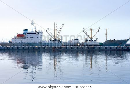 cargo ship docked and loading in port fully reflected in water